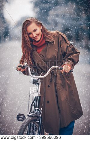 Happy girl rides a bike in a beautiful winter park, snowfall. Winter mood.