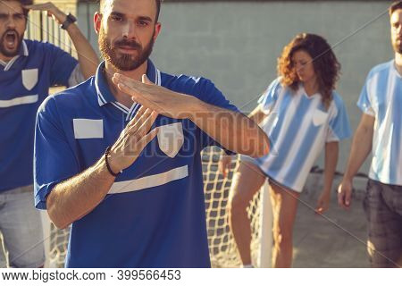 Group Of People Playing Football, One Of The Players Asking For Time Out After A Foul; People Angry
