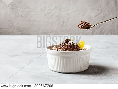 Chocolate Mousse Garnished With A Tangerine Wedge And White Chocolate Shavings In White Bowl And Tea