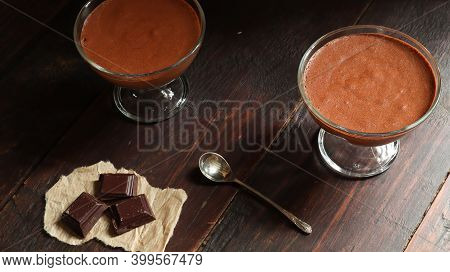 A Bowl With Chocolate Mousse, Pieces Of Dark Chocolate And A Teaspoon On The Old Dark Brown Table Ba
