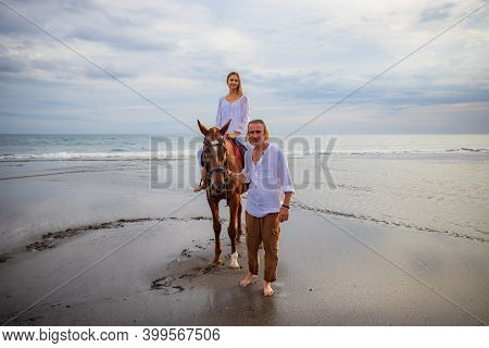 Horse Riding On The Beach. Woman On A Brown Horse. Man Leading Horse By Its Reins. Love To Animals.