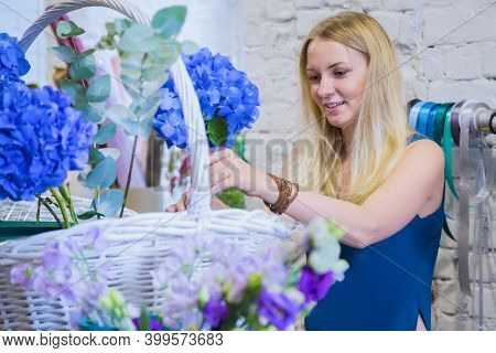 Professional Woman Floral Artist, Florist Smiling And Making Large Floral Basket With Flowers At Wor