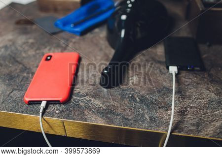 Charging Smartphone With Grey Portable External Battery Powerbank On Wooden Table .
