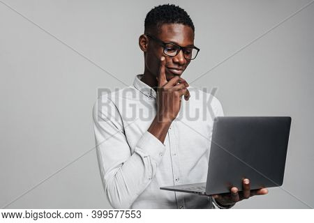 Handsome pensive young african business man using laptop computer isolated over gray background, wearing white formal shirt