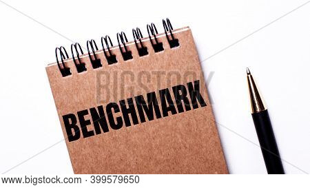 On A Light Background, A Black Pen And A Brown Notebook On Black Springs With The Inscription Benchm