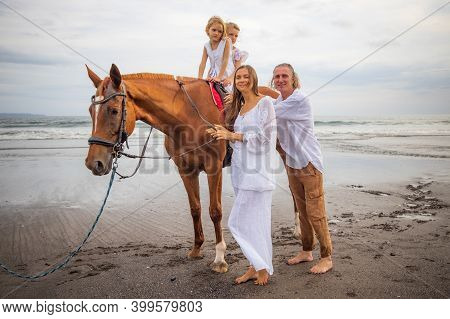 Horse Riding On The Beach. Two Sisters On A Horse. Mother Leading Horse By Its Rein. Father Standing