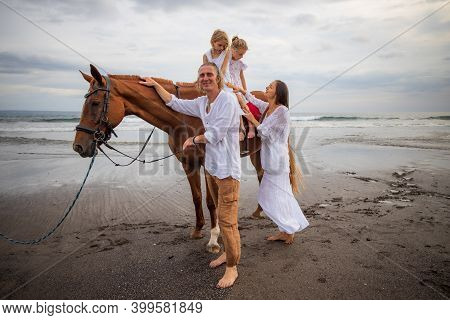 Horse Riding On The Beach. Two Sisters On A Horse. Father Leading Horse By Its Rein. Mother Standing