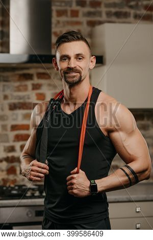 A Muscular Man In A Tank Top With A Pull Elastic Rope On The Shoulders Is Posing In His Apartment. T