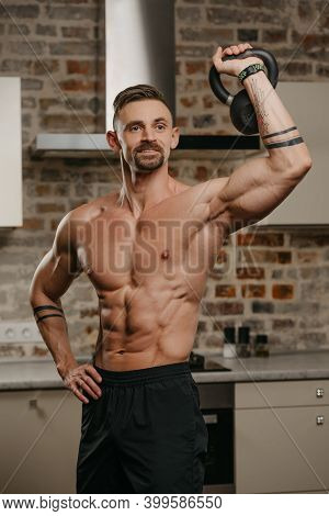 A Happy Muscular Man With A Beard Is Pushing A Black Weight In His Apartment. An Athlete With A Nake
