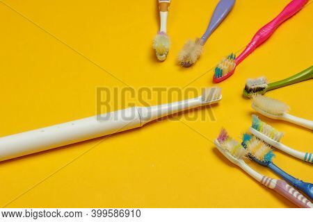 Modern Electric Toothbrush And Old Used Toothbrushes On Yellow Background. Top View