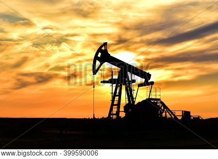 Crude Oil Pump Jack At Oilfield On Atmospheric Sunset Backround. Fossil Crude Output And Fuels Oil P