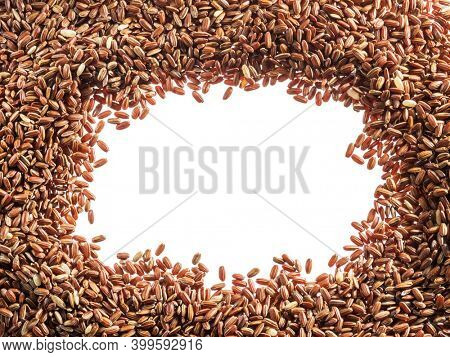 Brown rice - whole grain rice with outer hull or husk arranged as a frame. Top view.