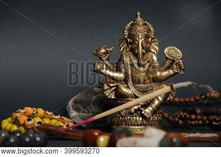 Occult Altar With Figurine Of God Ganesha, Candles, Aroma Stick, Stones. Black Background. Closeup