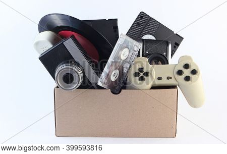 Cardboard Box With Video Cassettes, Retro Film Camera, Vinyl Record, Audio Cassette, Gamepad On A Wh