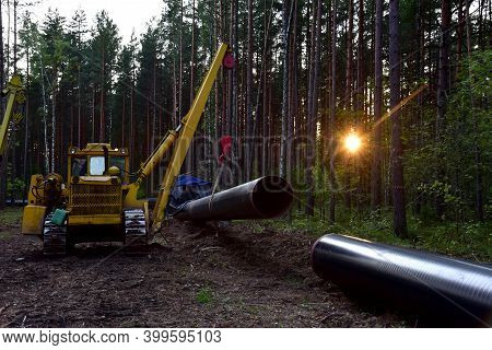 Construction Natural Gas Pipeline Project On Sunset Background. Crude Oil Transmission In Pipe To Ln