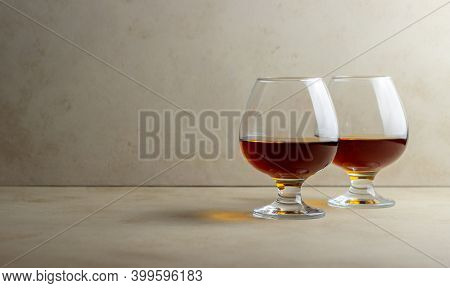 Cognac In A Glass On A Beige Background. Alcoholic Beverages. Bar
