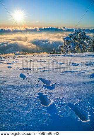 Beautiful winter cloudscape and sunrise in th? mountains . Deep footsteps on the foreground.