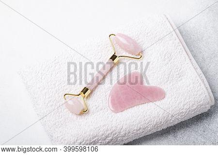 Rose Quartz Jade Roller And Gua Sha Massager On White Towel. Massage Tool For Facial Skin Care, Spa