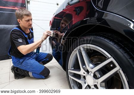 The Process Of Applying A Nano-ceramic Coating On The Car's Bumper By A Male Worker With A Sponge An