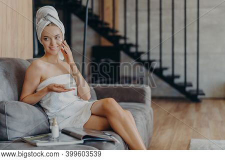 Pretty Smiling European Woman Applies Face Cream On Face, Holds Jar Of Cosmetic Product, Takes Care