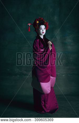 Beauty. Young Japanese Woman As Geisha Isolated On Dark Green Background. Retro Style, Comparison Of