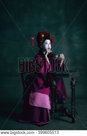 Having Fun. Young Japanese Woman As Geisha Isolated On Dark Green Background. Retro Style, Compariso