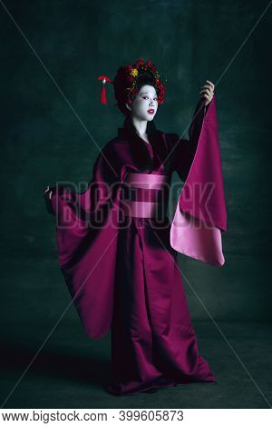 Gorgeous. Young Japanese Woman As Geisha Isolated On Dark Green Background. Retro Style, Comparison