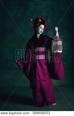 Golden Bird. Young Japanese Woman As Geisha Isolated On Dark Green Background. Retro Style, Comparis