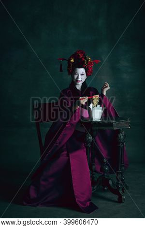 Delicious Food. Young Japanese Woman As Geisha Isolated On Dark Green Background. Retro Style, Compa