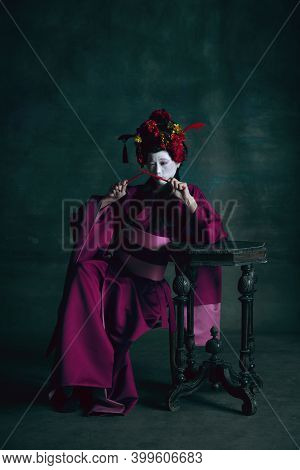 Playing With Chopsticks. Young Japanese Woman As Geisha Isolated On Dark Green Background. Retro Sty