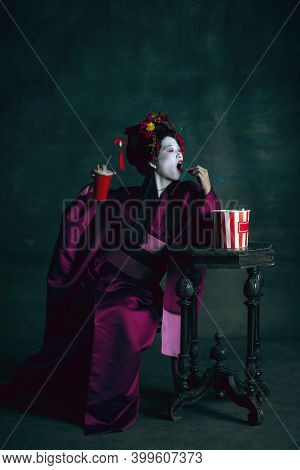 Fastfood Lover. Young Japanese Woman As Geisha Isolated On Dark Green Background. Retro Style, Compa