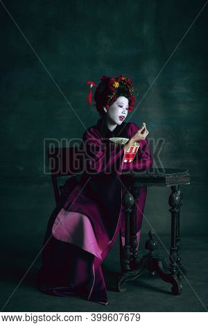 Popcorn Tasty. Young Japanese Woman As Geisha Isolated On Dark Green Background. Retro Style, Compar