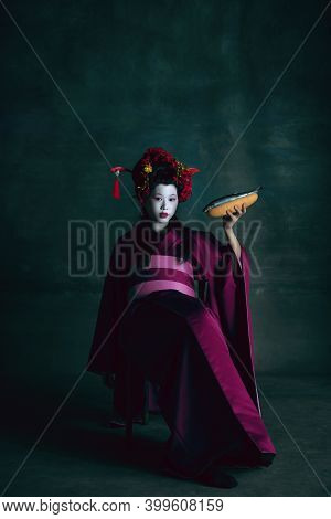 Tasty Cuisine. Young Japanese Woman As Geisha Isolated On Dark Green Background. Retro Style, Compar