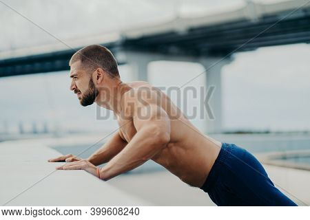 Horizontal Shot Of Fit Man With Strong Arms Muscular Body Does Push Up Exercises Outdoor, Has Thick