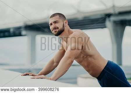 Side View Of Athletic Motivated Purposeful Bearded Sportive Bare Chested Man Performs Push Ups Exerc