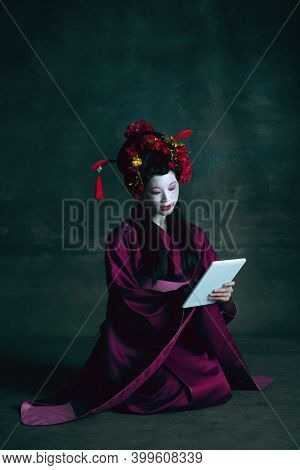 Scrolling Tablet. Young Japanese Woman As Geisha Isolated On Dark Green Background. Retro Style, Com