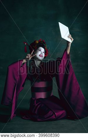 Taking Selfie, Blogger. Young Japanese Woman As Geisha Isolated On Dark Green Background. Retro Styl
