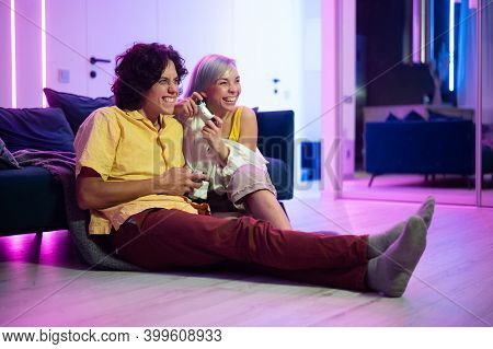 Young Couple Playing Video Games While Sitting On The Living Room Floor Lit With Neon Color.