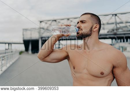 Horizontal Outdoor Shot Of Sporty Bearded Athlete Man Drinks Water After Training, Holds Bottle Of R