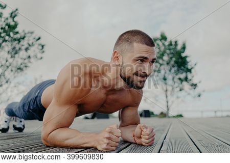 Athletic Guy Stands In Plank Pose To Keep Fit, Leads Healthy Lifestyle And Poses Outdoor. Young Bear