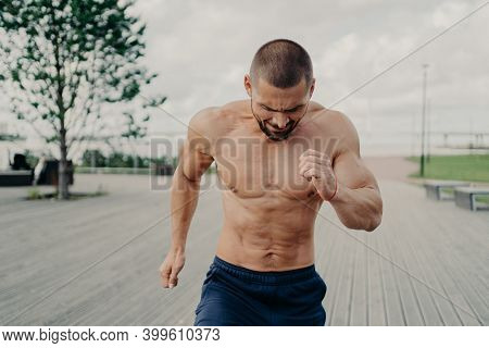 Sporty Energized Bearded Male Runner Goes Jogging On Walkway Next To River Or Sea, Has Daily Trainin