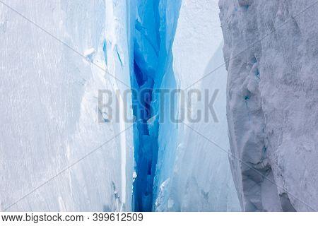Deep Blue Crack In A Glacier In Antarctica. Close-up. A Break In The Glacier. Global Warming.