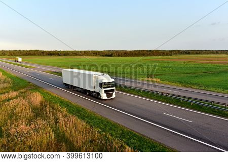 Truck With Semi-trailer Driving Along Highway On The Blye Sky Background. Goods Delivery By Roads. S