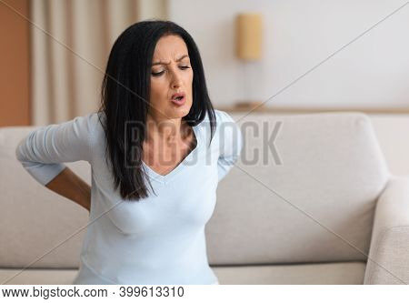 Rheumatism. Brunette Mature Woman Having Back Pain While Sitting On The Couch At Home, Suffering Fro