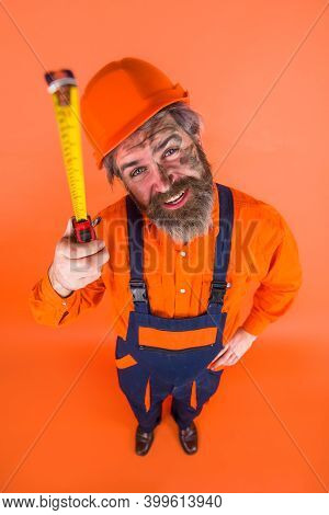 Builder With Measure Tape. Construction Worker. Worker Use Tape Measure. Builder Equipment. Measurin