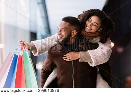 Healthy Relationship. Smiling African American Man Giving Piggyback Ride To His Happy Woman Who Hold