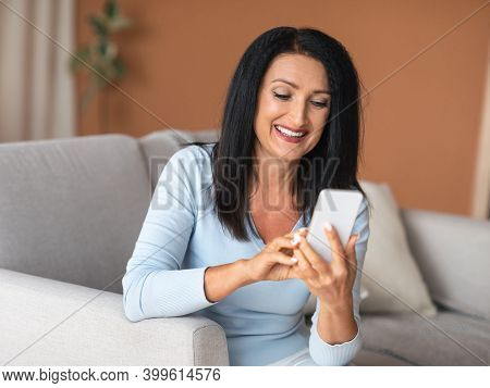 Lifestyle Concept. Portrait Of Cheerful Smiling Senior Woman Holding And Using Her Mobile Phone, Cha