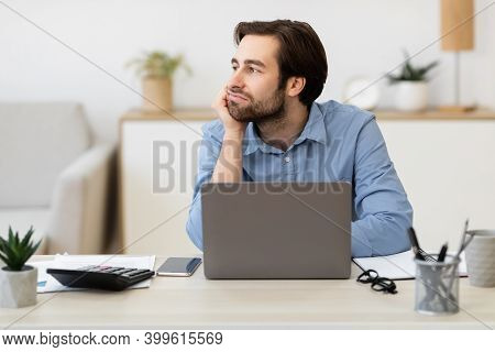 Boring Job. Bored Businessman Sitting At Laptop Computer And Looking Aside Procrastinating In Modern