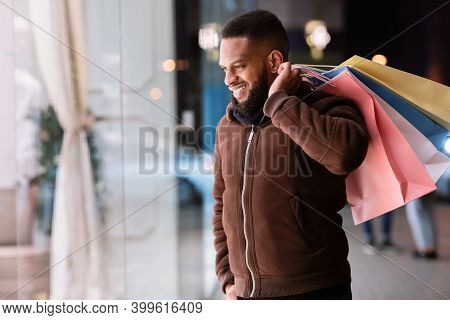 Consumerism Concept. Satisfied Glad African American Man Looking At The Store Window Of The Mall. Sm