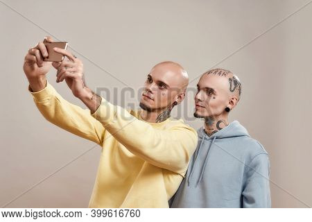 Photo With Best Friend. Two Young Caucasian Twin Brothers In Casual Wear Taking Selfie On Mobile Pho